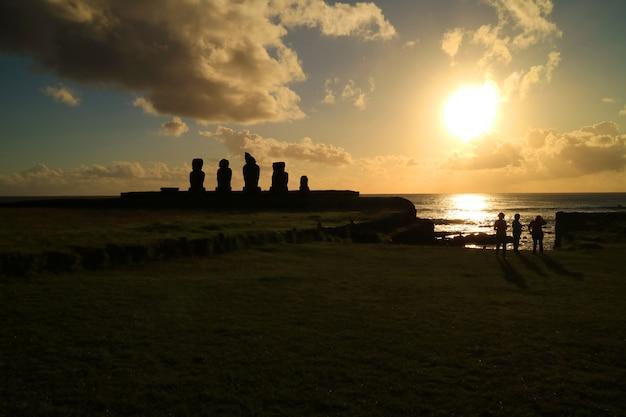 Gente viendo la puesta de sol sobre el océano pacífico en ahu tahai con estatuas moai, isla de pascua, chile