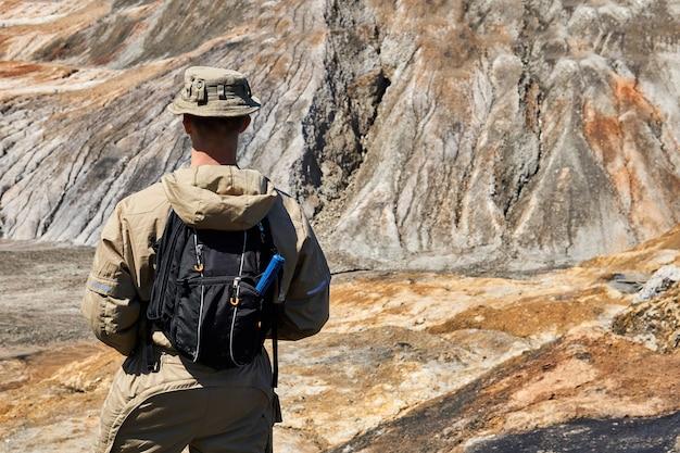 Geólogo masculino en una expedición entre un paisaje de barrancos desérticos, vista desde la parte posterior