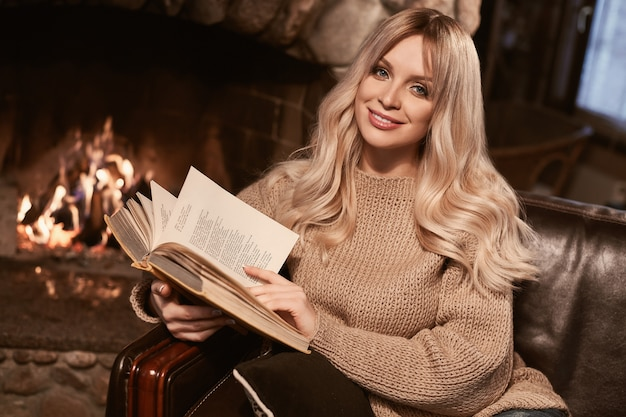 Georgeous elegante rubia con libro cerca de la chimenea