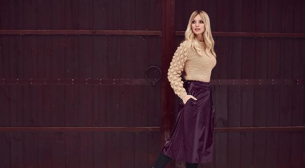 Georgeous elegante rubia en vestido brillante sobre fondo de madera