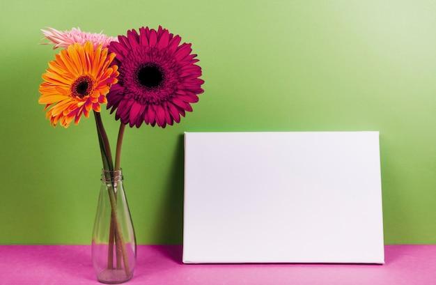 Gerbera florece en el florero cerca de la tarjeta en blanco en el escritorio rosado contra la pared verde