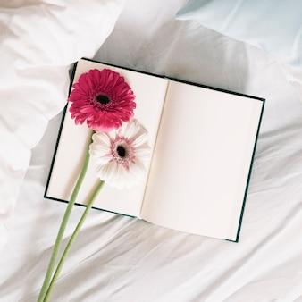 Gerberas y cuaderno en la cama