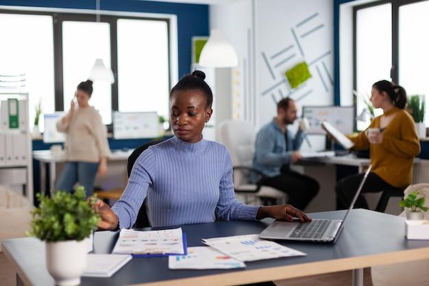 Gerente africano y compañeros de trabajo en la oficina corporativa concentrados en nuevos negocios