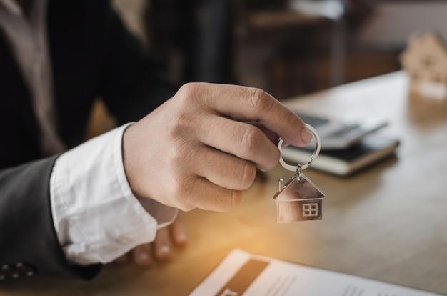 Gerente de agente de bienes raíces que da la llave de la casa al cliente después de firmar el contrato