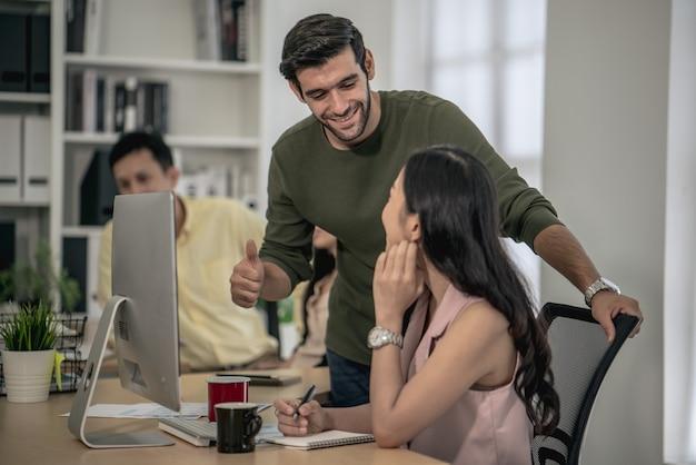 El gerente anima a admirar a los trabajadores de oficina que pueden hacer el plan de trabajo de la empresa objetivo.