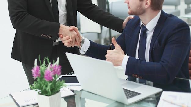 Gerente de apretón de manos y cliente, cerca de la mesa en la oficina.foto con espacio de copia.