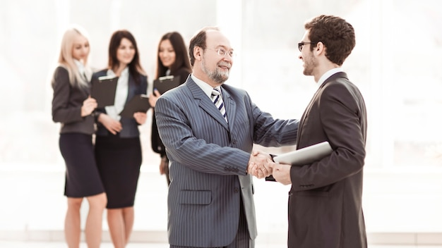 Gerente de apretón de manos y cliente en el fondo del equipo empresarial en una oficina moderna