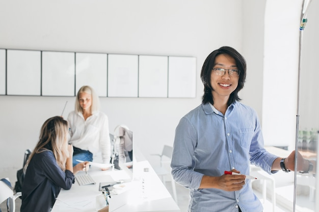 Gerente asiático con sonrisa sincera posando junto al rotafolio mientras las niñas hablan
