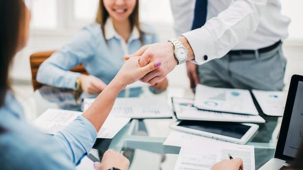 El gerente del banco y el cliente se dan la mano después de firmar un lucrativo contrato en el fondo de la oficina moderna