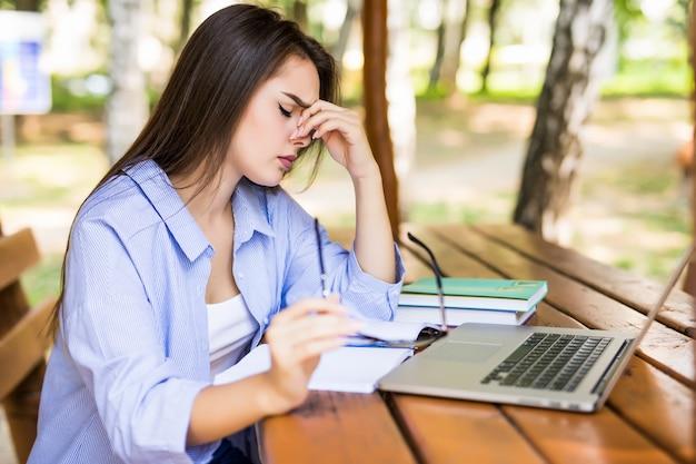 Gerente cansado usando una computadora portátil en una mesa del parque al final del día