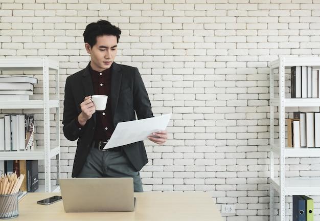 Gerente de la compañía masculina asiática de pie en un escritorio en la oficina, sosteniendo una taza de café, leyendo información de la reunión, documentos o currículum de nuevos empleados que esperan entrevistas de trabajo.