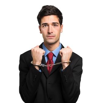 Gerente con las manos esposadas en su oficina, triste