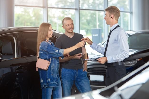 El gerente del concesionario de automóviles felicita por la compra de un automóvil nuevo y entrega las llaves a la pareja