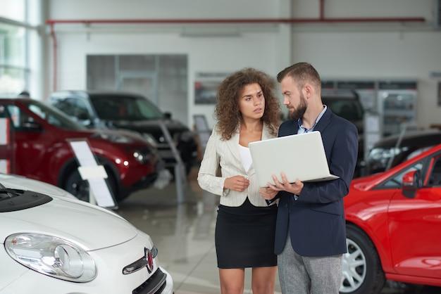 Gerente de concesionario de automóviles mostrando automóvil a mujer.