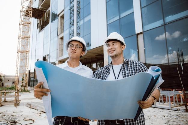Gerente de construcción y equipo de ingenieros que controlan el plan en el sitio de construcción. equipo de tránsito de teodolito. equipo de ingenieros. trabajando en obra.