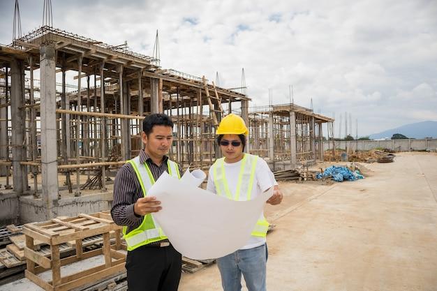 Gerente de construcción de hombre de negocios asiático y trabajador ingeniero en casco protector sostienen papel de planos a mano en el sitio de construcción de viviendas