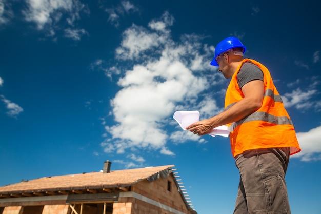 Gerente de construcción o sitio que supervisa la construcción del nuevo edificio con un proyecto de construcción, desarrollo de concepto