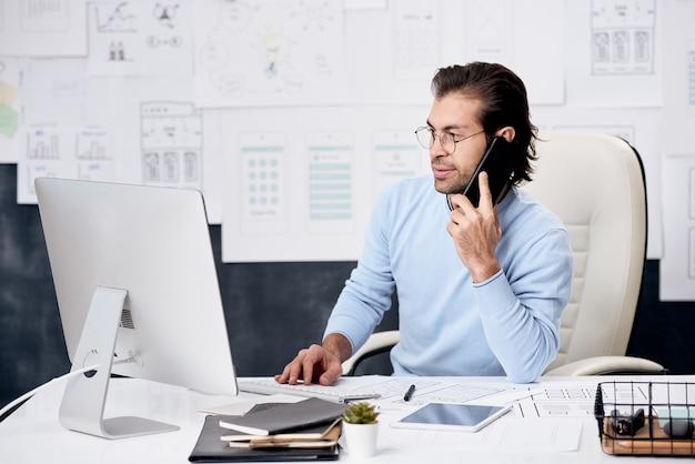 Gerente de contenido de cabello castaño de la compañía de ti sentado en el escritorio y hablando con un colega por teléfono mientras analiza datos en la computadora