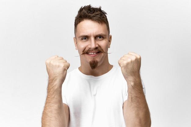 Gerente creativo exitoso con barba de chivo y bigote posando aislado manteniendo los puños cerrados y sonriendo ampliamente, emocionado y orgulloso por la promoción inesperada en el trabajo o el aumento de salario.