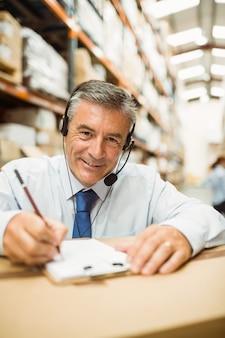 Gerente de almacén sonriente escribiendo en portapapeles en un gran almacén