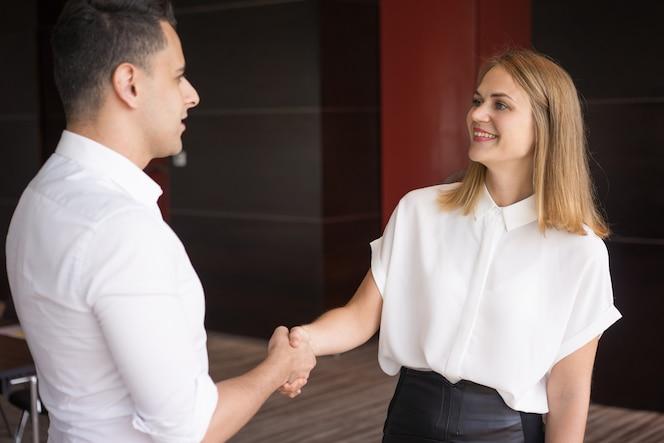 Gerente de sexo femenino feliz que saluda al socio masculino con apretón de manos.