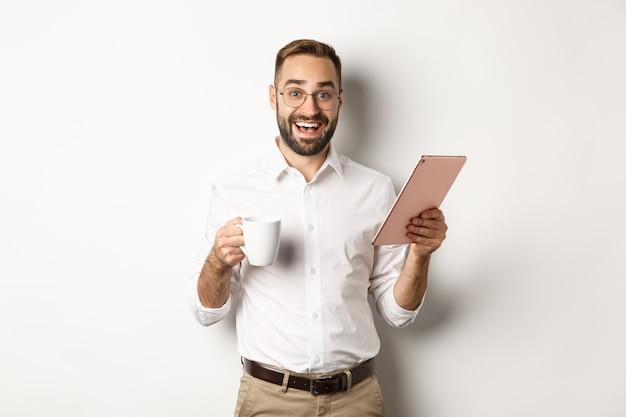 Gerente emocionado leyendo en tableta digital, trabajando y tomando café, de pie contra el fondo blanco.