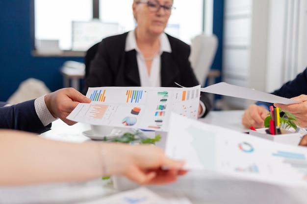Gerente de la empresa confiado que da tareas de trabajo a diversos trabajadores en equipo que analizan el papeleo con gráficos sentado en la oficina de puesta en marcha