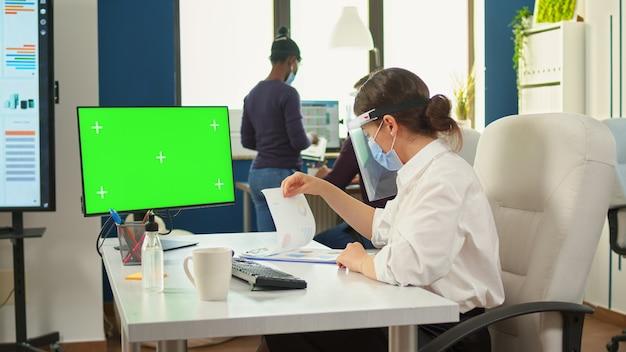 Gerente de la empresa con mascarilla escribiendo en computadora con pantalla verde en la nueva oficina comercial normal respetando la distancia social durante la pandemia global. mujer mirando maqueta, espacio de copia, pantalla de croma