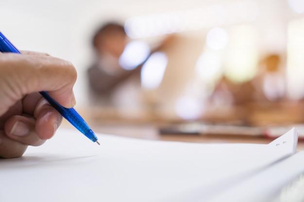 Gerente de empresario con pluma azul para comprobar y firmar documentos blancos