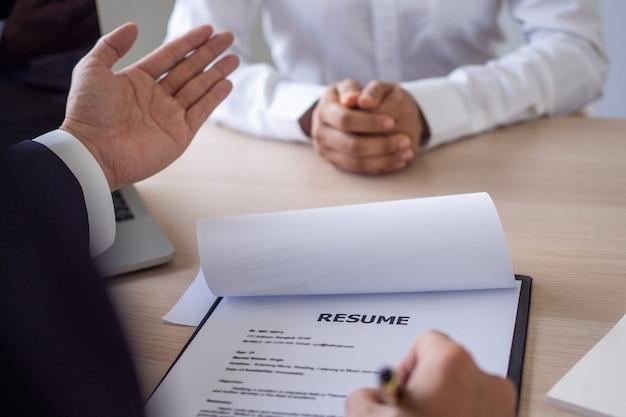 El gerente entrevista a los solicitantes o candidatos y lee el currículum. el gerente pregunta sobre la experiencia laboral y comenta la actitud hacia la empresa.