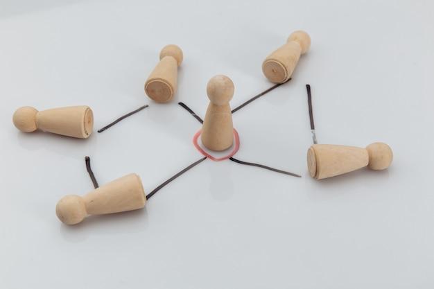 Gerente y equipo. figuras de madera sobre una mesa blanca. concepto de teambuilding, liderazgo y gestión.