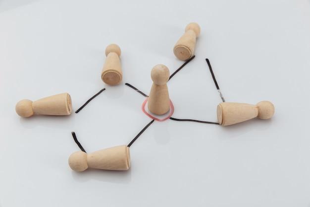 Gerente y equipo. figuras de madera sobre una pared blanca. concepto de teambuilding, liderazgo y gestión.