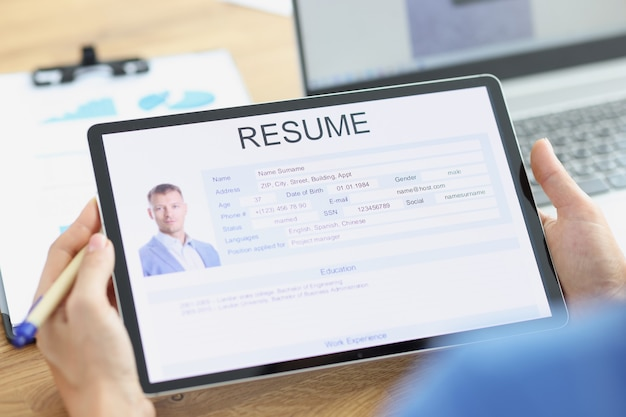 El gerente examina el cuestionario electrónico del solicitante sobre la búsqueda de empleo de la tableta y la redacción del currículum