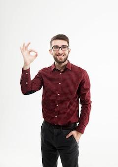 Gerente exitoso haciendo el gesto ok sobre un fondo blanco.