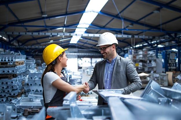 Gerente de fábrica visitando la línea de producción y felicitando al trabajador por la promoción por su arduo trabajo y buenos resultados