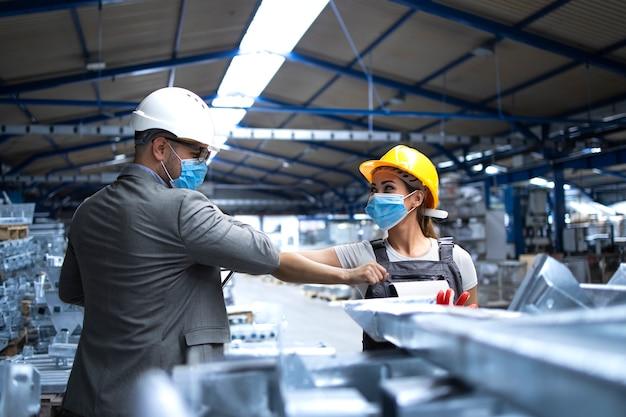 Gerente de fábrica visitando la línea de producción y saludando al trabajador con los codos debido al virus corona