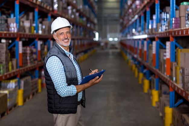 Gerente feliz sosteniendo un portapapeles y posando durante el trabajo