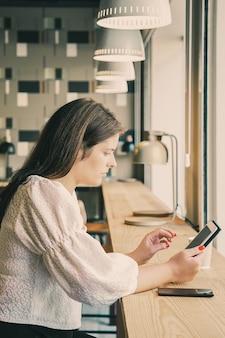 Gerente femenina enfocada usando tableta mientras está sentado en el escritorio en el espacio de trabajo conjunto o en la cafetería