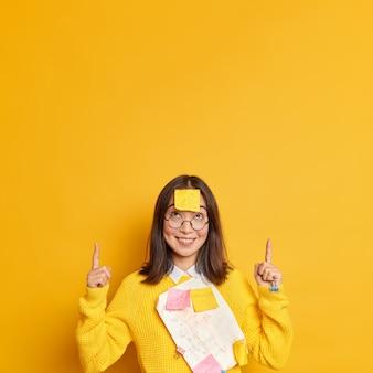 Gerente femenina exitosa positiva en suéter casual con papeles y pegatinas pegadas por clips, sonrisas y puntos en el espacio de la copia