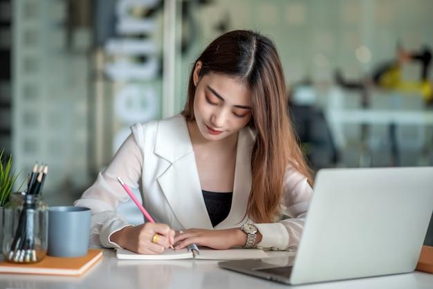Gerente financiero asiático hermoso que trabaja en la oficina moderna en la computadora portátil