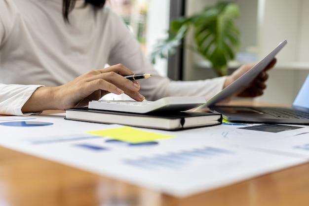 El gerente de finanzas de la empresa está usando una calculadora, usa una calculadora para calcular los números en los documentos financieros de la empresa que los empleados del departamento crean como documentos de reuniones.