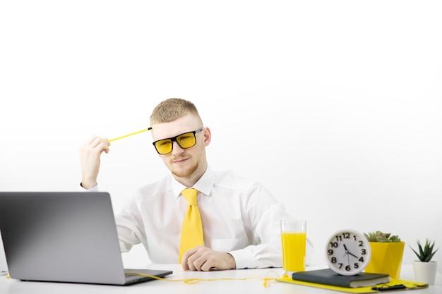 El gerente de gafas amarillas mira atentamente la computadora portátil, acentúa la olla amarilla