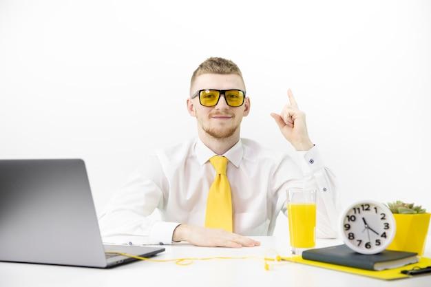 El gerente con gafas amarillas señala con el dedo hacia arriba, acentúa la olla de jugo de corbata amarilla
