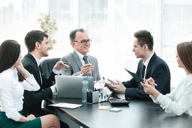 Gerente y grupo empresarial discutiendo documentos financieros días laborables de oficina.