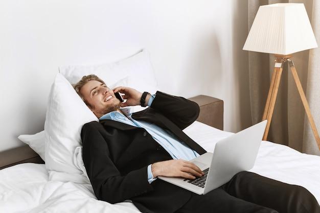 Gerente guapo y feliz con elegante corte de pelo y barba acostado en la cama en la habitación del hotel, hablando por teléfono y revisando su trabajo en la computadora portátil antes de la reunión de negocios