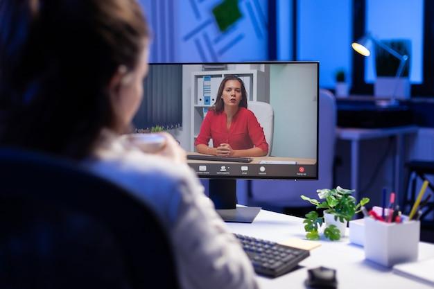 Gerente hablando con compañeros de equipo durante la teleconferencia en línea a la medianoche desde la estrategia de marketing de planificación de la oficina de negocios