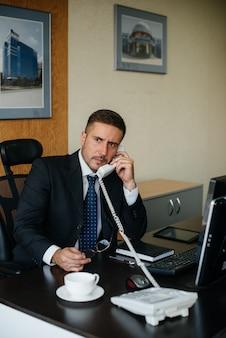 El gerente está hablando por teléfono en su oficina.