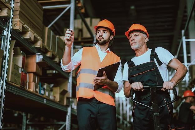 Gerente en hardhat hablando con un trabajador de almacén