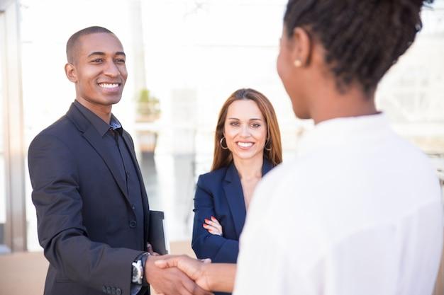 Gerente hombre afroamericano feliz estrechar la mano de la pareja