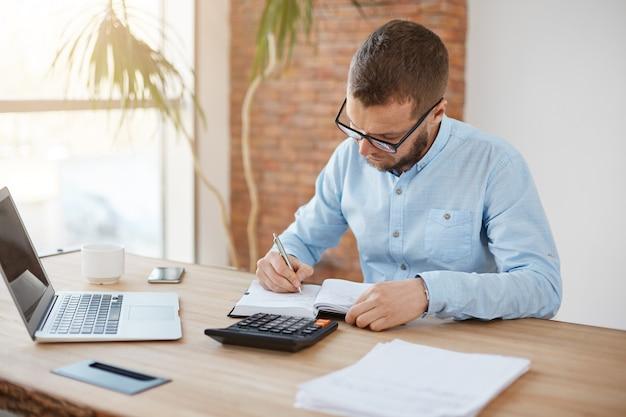 Gerente hombre caucásico joven con gafas sentado en la oficina de la empresa